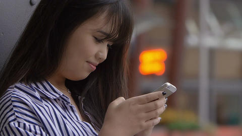 young chinese woman chatting on facebook with her mobile phone: texting message Footage