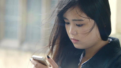 young and beautiful chinese using cell phone to send messages ビデオ