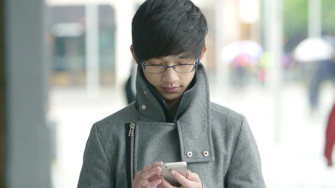 young adult chinese man using smartphone in the city Footage