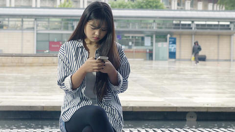 young adult chinese woman chatting using social networks on the mobile phone Footage