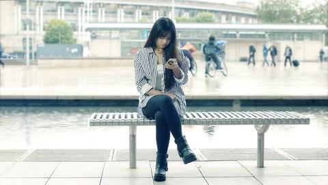 young beautiful chinese woman using smartphone sitting on a bench Footage