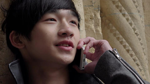 young chinese man talking with someone using a cell phone Footage