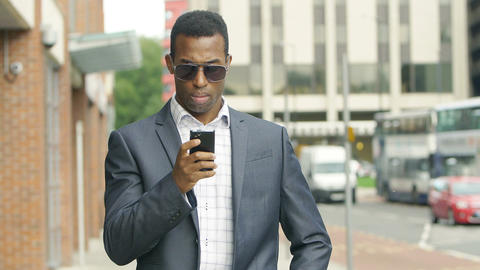 black casual elegant businessman in the city using a smartphone Footage