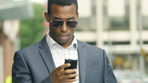 handsome black businessman texting a message on the smartphone Footage