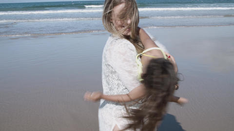 Cute little girl running on beach to her happy mom Acción en vivo