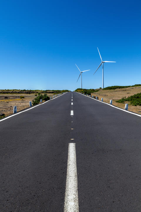 a straight road with two wind turbines over the area with a blue sky Fotografía