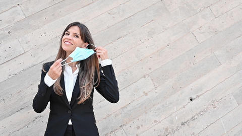 Happy business woman removes a medical mask. A smiling woman in a suit enjoys Live Action
