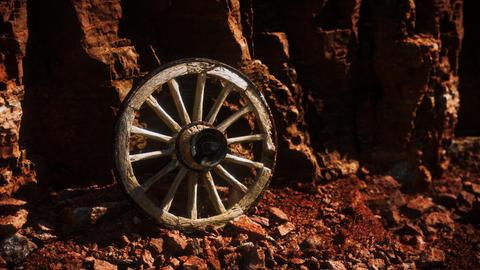 old wooden cart wheel on stone rocks GIF