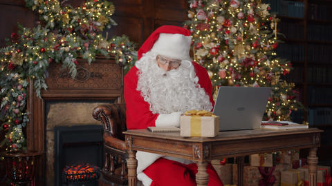 Man in Santa Claus costume working with computer indoors in decorated house Live Action