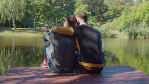 Rear view of gay couple embracing on jetty by lake Live Action