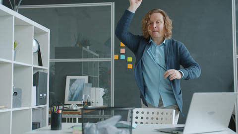Joyful man playing game in office throwing paper balls in bin having fun alone Live Action