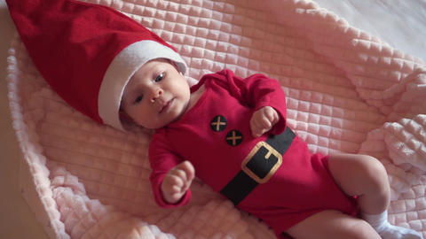 Cute Baby Santa lying in a suit of Santa Claus, in a red hat, red pajamas Live Action