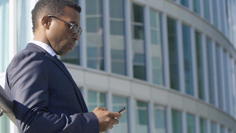 handsome young businessman (African-american) with smartphone Live Action