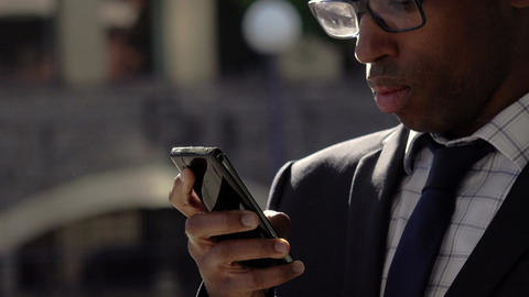 elegant black businessman using smartphone: corporate suits, handsome 30s black Footage