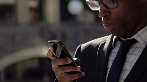 elegant black businessman using smartphone: corporate suits, handsome 30s black Footage
