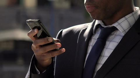 business suit: elegant businessman using smartphone: texting, typing messages Footage