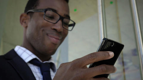 handsome black businessman reads a message on the smartphone and smiles Footage