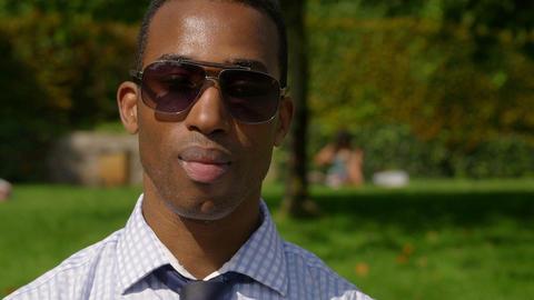 elegant African american businessman smiles in camera in the park Footage
