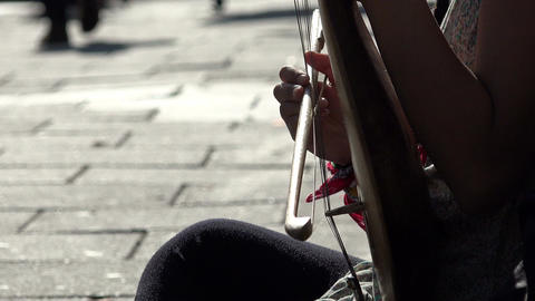 playing a string instrument: bow, melody, street music, street artist Footage