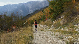 young woman skyrunner with walking sticks running from hill on a mountain trail Footage