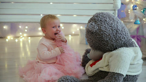 Little girl is crying with bear sitting on the floor Footage