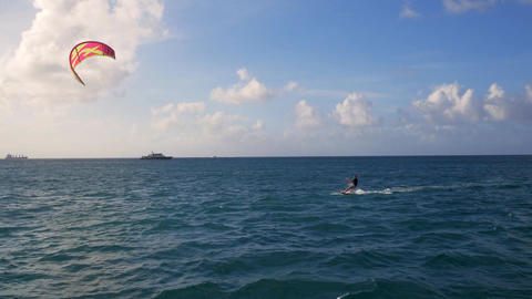 Man kite surfing wind surfing in tropical ocean Live Action