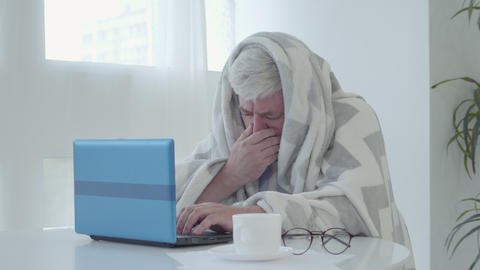 Exhausted ill mid-adult man wrapped in blanket rubbing nose and coughing as Live Action