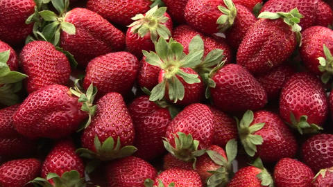 A pile of strawberries sits on a table Stock Video Footage