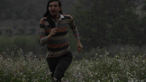 A man acts silly in a field of wildflowers Footage