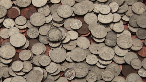 A pile of American coins lies spread out on a surface Footage