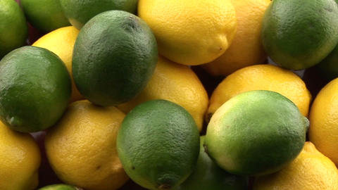 Yellow lemons sit in a pile with green limes Footage