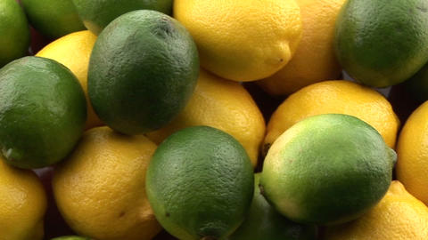 Yellow lemons sit in a pile with green limes Stock Video Footage