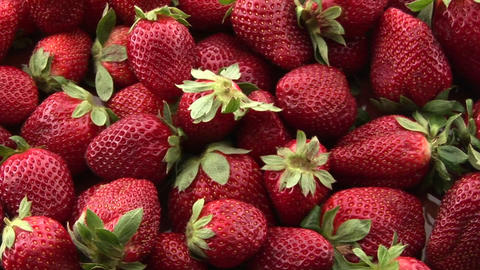 Red strawberries sit in a pile on a surface Footage