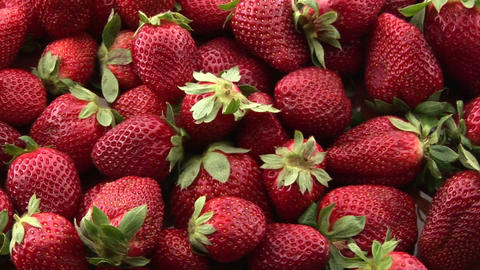 Red strawberries sit in a pile on a surface Stock Video Footage