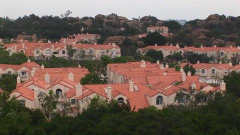 Thick vegetation surrounds a neighborhood of stucco homes Stock Video Footage