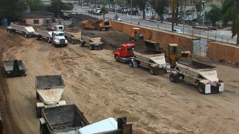 Trucks move dirt at a construction site Footage