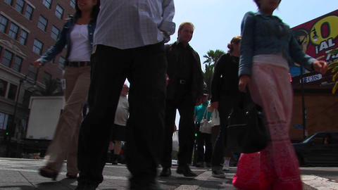 Pedestrians cross a street at an intersection Stock Video Footage