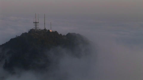 A time lapse of heavy cloud cover over antennas on a mountain top Footage