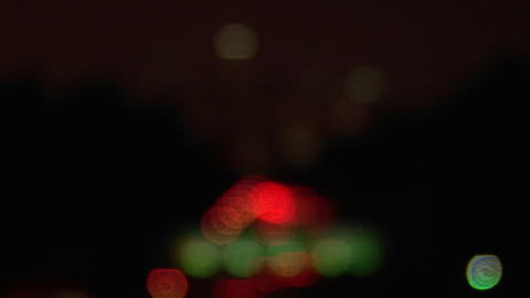 A rack-focus of vehicles driving on the freeway and into the city at night Footage