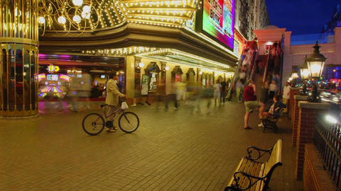 A time lapse at night of people sitting and walking in Las Vegas Footage