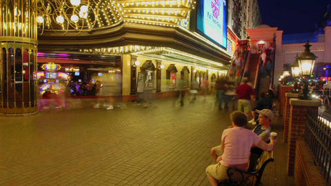 A time lapse at night of people sitting and walking in... Stock Video Footage