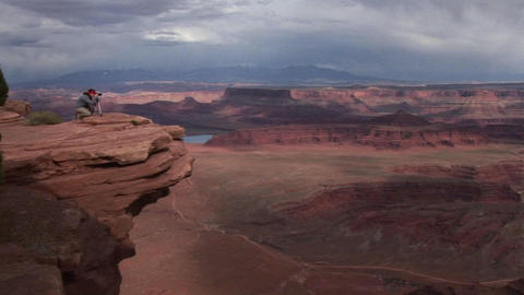 A photographer walks to a ledge that overlooks a valley of mesas at day in Canyonlands National Park Footage