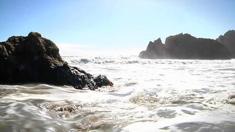 Waves roll into shore on a sunny day along California coastline Footage