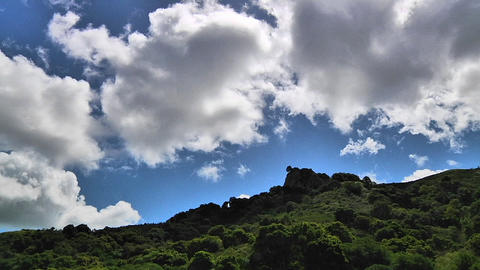 Time lapse of clouds passing over a green mountainside Stock Video Footage