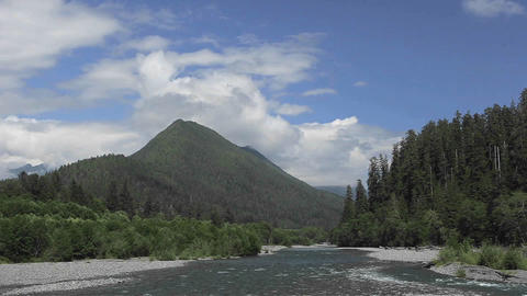 Time lapse of clouds passing over a forest, mountains and river Footage