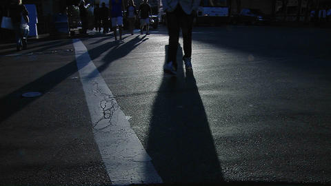 Pedestrians pass in a crosswalk on a busy city street as long shadows stretch along the pavement ビデオ