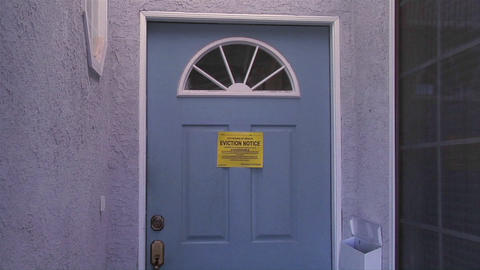 A slow move into a door with an eviction notice signals... Stock Video Footage