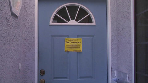 A slow move into a door with an eviction notice signals the worldwide mortgage crisis Footage