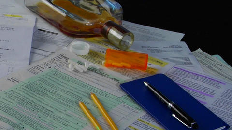 A checkbook, empty glass of liquor and pills suggest that... Stock Video Footage