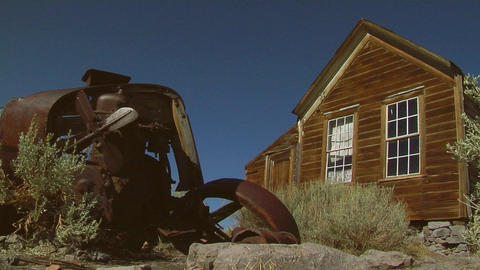 An old rusting car sits near an abandoned building in the ghost town of Bodie Footage